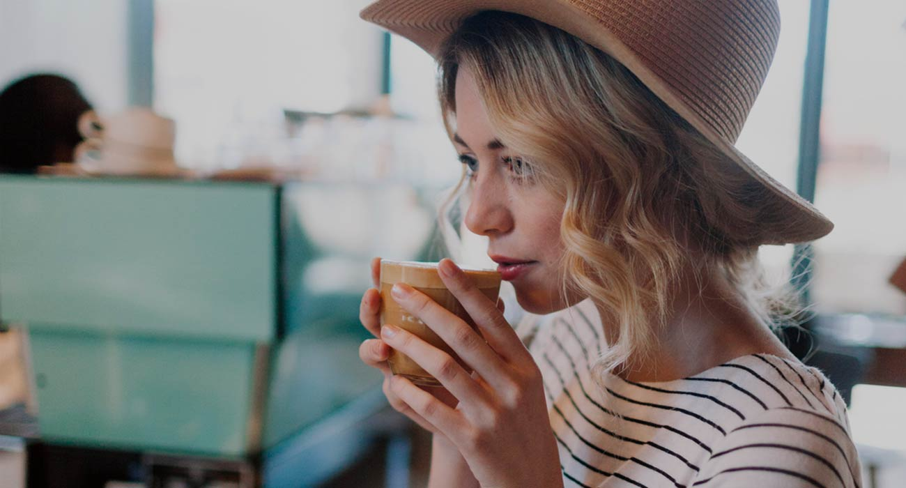 Woman sipping coffee at a cafe
