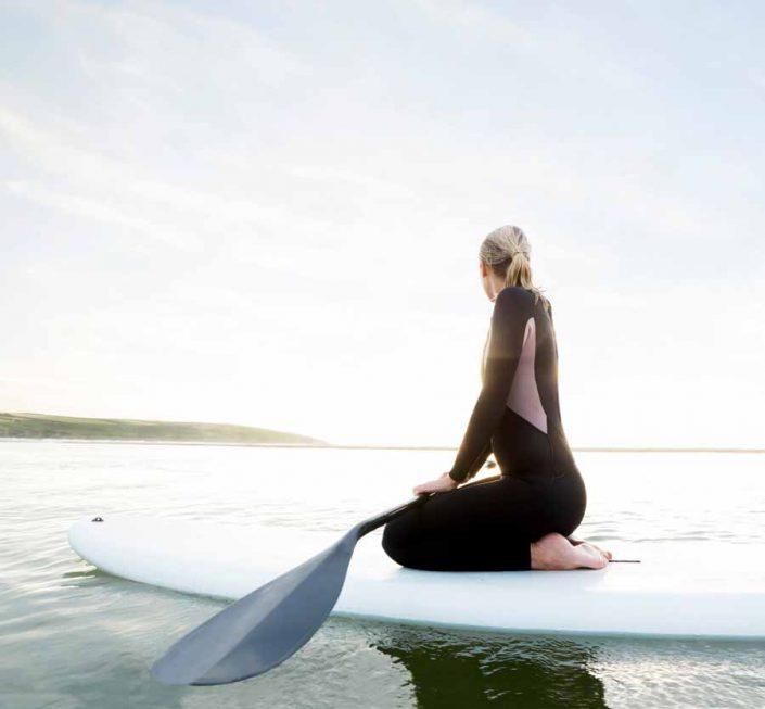 Woman on kneeling on paddleboard