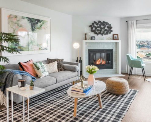 apartment living room with fireplace, window, and plants