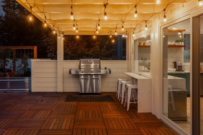 outdoor BBQ with bistro lights above on a back deck.