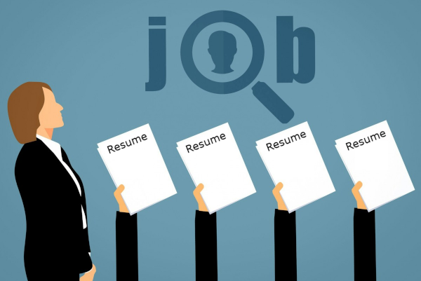 four people handing resumes to recruiter