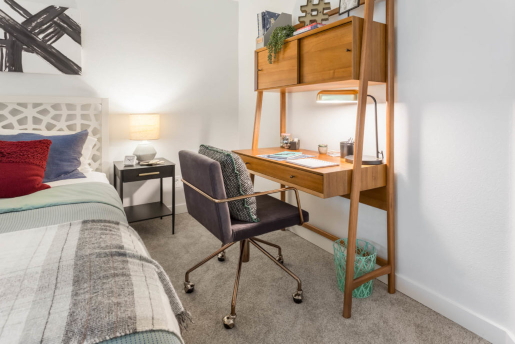 small wooden desk with office chair next to bed