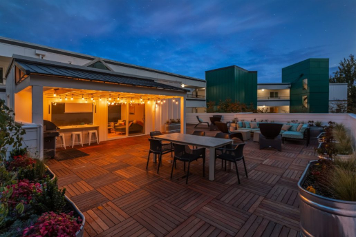 rooftop lounge in evening with rooftop garden, tables, couches, and playful lighting