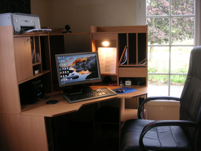 home office corner desk by window with blooming tree outside, black office chair facing computer on organized desk with printer and webcam